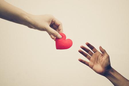 남성의 손에 붉은 마음을주는 여성의 손을
