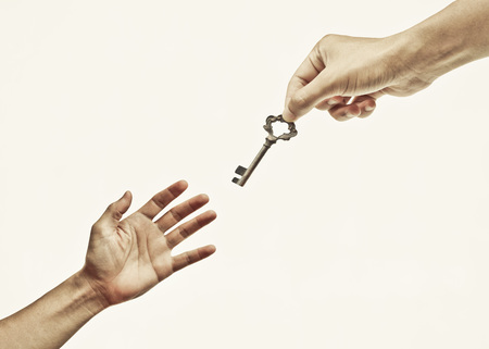 giving: hand giving a key to a hand - giving help, opportunity, success concept Stock Photo