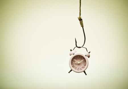 A clock hung on a fish hook - Time trap concept Reklamní fotografie - 45691519