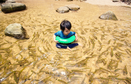 surrounded: Huay Luang waterfall, Ubon Ratchathani, Thailand - a boy playing in a clear water surrounded by many fish