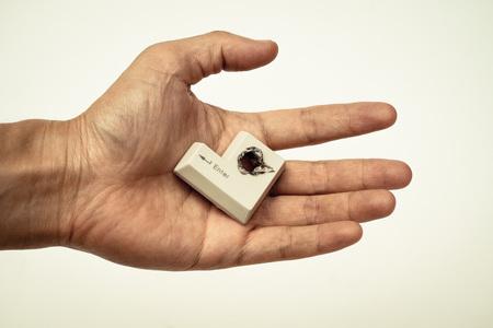 penetración: equipo de la mano de hackers tecla de confirmación con un concepto de violación de la seguridad informática orificio