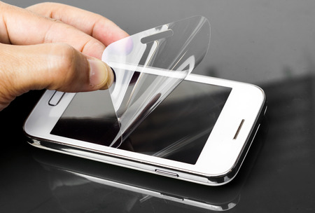 hand laying scratch protective film on a smartphone screen