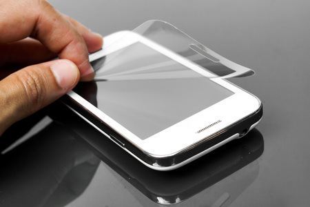protective: hand laying scratch protective film on a smartphone screen