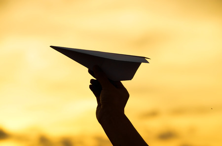 hand holding a paper plane against sunset sky
