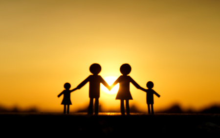 human hands: Abstract blurred background of paper cut of family with sunset background  Family Life Insurance  Protecting family  Family concepts Stock Photo