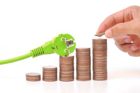 energy bar: hand putting coins to a pile of golden coins with a green plug  green energy concept