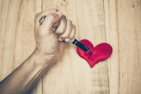 hatred: hand with a knife stabbing into a red heart Stock Photo