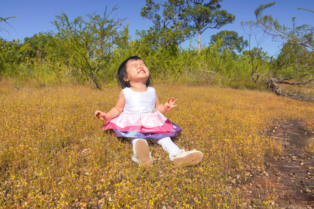 baby sit: baby girl sitting in a field with yellow flowers