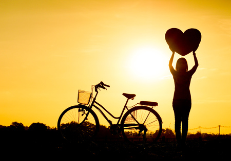 lonely heart: Silhouette of a woman with a bicycle and holding big hearts