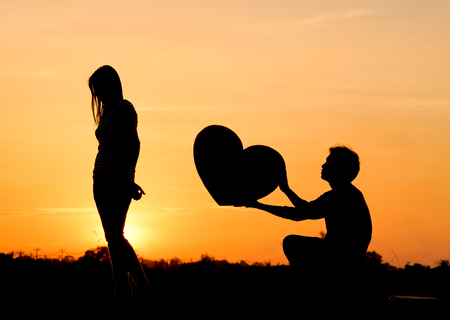 to confess love: Man begging a woman for love by giving a big heart