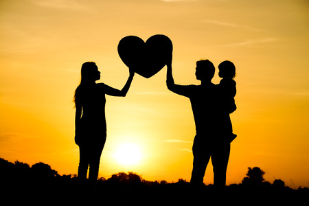 Silhouette of a family comprising a father, mother, and a child  Family love concept Stockfoto