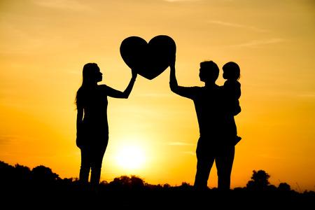 silueta niño: Silueta de una familia constituida por el padre, la madre, y un concepto de amor de la familia del niño Foto de archivo