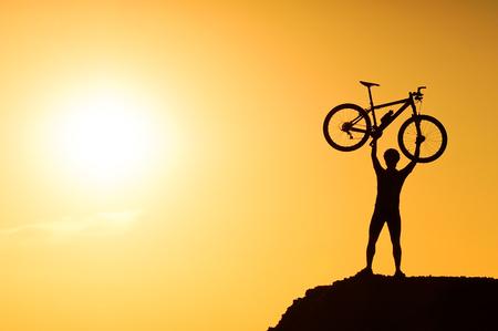 race: silhouette of a mountain bike cyclist standing on the mountain raising his bike Stock Photo