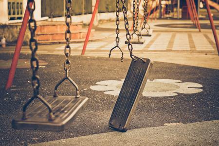Broken chain swing in playground Stockfoto