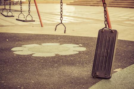 lonliness: Broken chain swing in playground Stock Photo