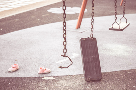 chain swing ride: Broken chain swing in playground and kid shoes in vintage tone  Accident and injury in the playground concept