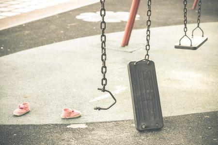 ビンテージ トーン事故の遊び場や子供の靴や遊び場コンセプトに怪我で壊れたチェーン スイング 写真素材