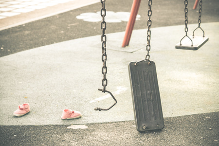 Broken chain swing in playground and kid shoes in vintage tone  Accident and injury in the playground concept