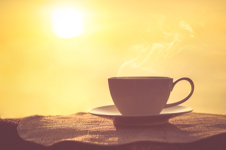 jot: Silhouettes of sunrise morning coffee with a note and a pen