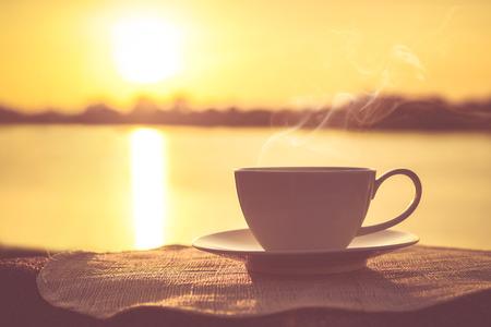 Silhouettes de café du matin au lever du soleil avec une note et un stylo Banque d'images