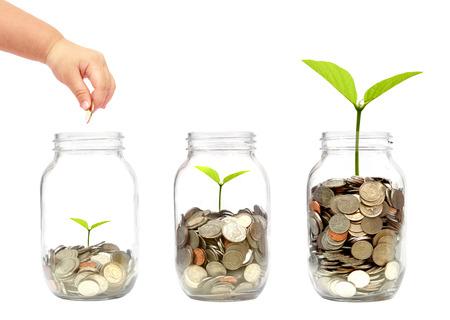 Hand van het kind zetten een gouden munt in een fles met een groene plant groeit op muntstukken Stockfoto - 52851171