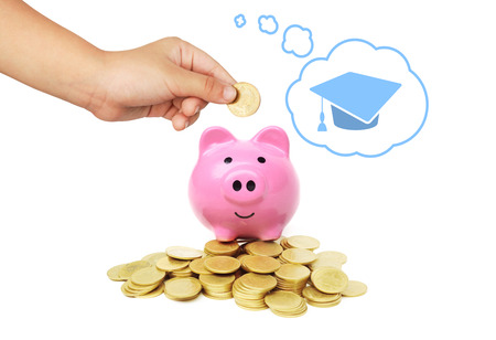 hand of a young female child putting a coin into a pink piggy bank thinking of education - kid saving money for future concept