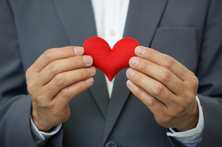 man business oriented: Businessman holding a red heart - crm - service mind Stock Photo
