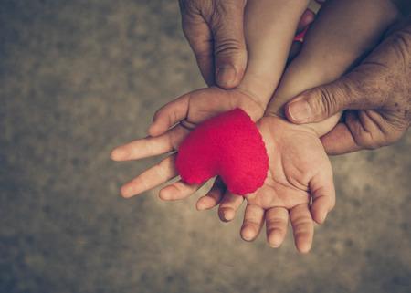 vieilles mains tenant jeune main d'un bébé avec le coeur rouge