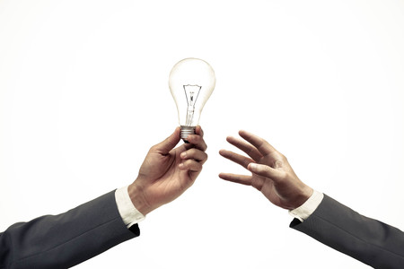 new idea: Hand of a businessman giving a light bulb to other businessman  Business needs new idea and innovation concept