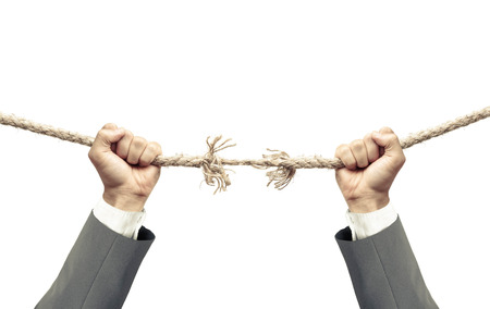 apart: Hand of a businessman hung on almost torn apart rope - Business risk concept