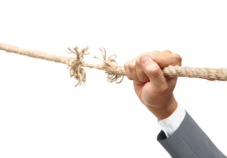 frailty: Hand of a businessman hung on almost torn apart rope - Business risk concept
