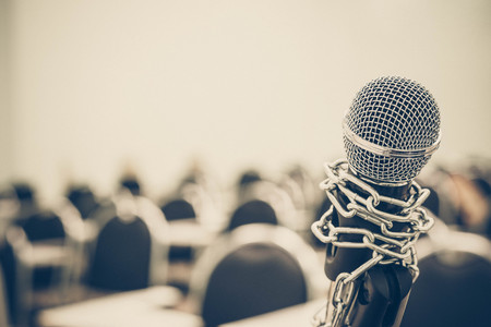 oppress: A chained microphone - Freedom of the press is oppressed.