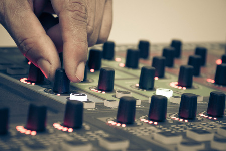 adjusting: Hand adjusting audio controller Stock Photo