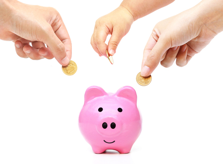 Father, mother, and baby in the family do saving money in pink piggy bank Stockfoto