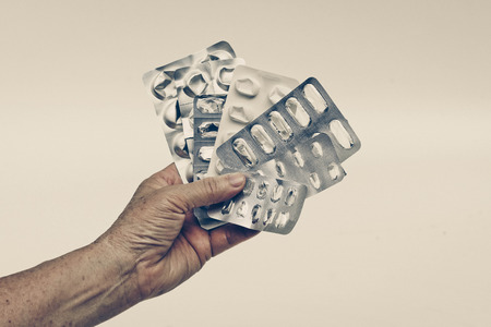overuse: Patients hand holding a collection of used tablets covers in vintage tone - Drug overuse - drug abuse concept