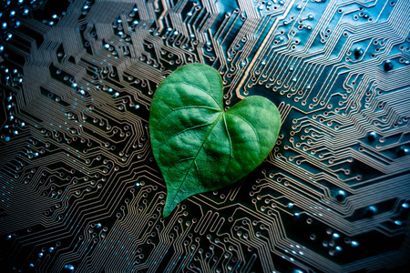 A green leaf with a heart shape on a computer circuit board  green it  green computing  csr  it ethics