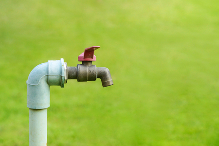 usage: A tap with green grass background  Water consumption and usage concept Stock Photo