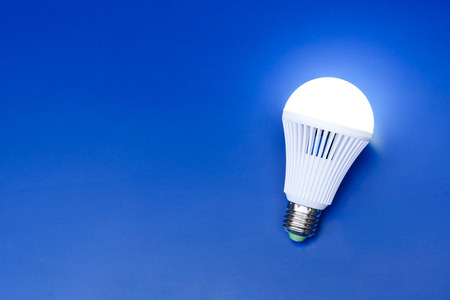 A turned on LED light bulb on blue background  Using economical and environmentally friendly light bulb concept
