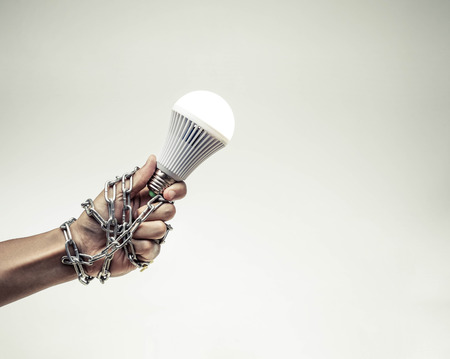 freedom of thought: A turned on LED light bulb chained and lock  Something stops new idea  Freedom of thought