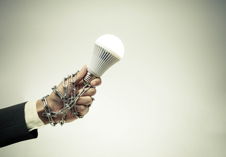 restrain: Hand holding a turned on LED light bulb chained and lock  Something stops new idea  Freedom of thought