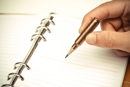 A rifle bullet with a pencil at the head  Using idea as weapon concept Stock Photo