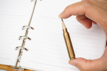 oppress: A rifle bullet with a pencil at the head  Using idea as weapon concept Stock Photo