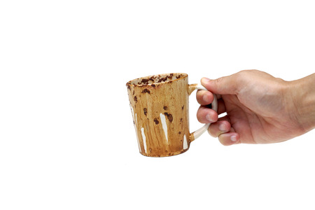 spat: Hand holding a dirty cup of coffee after heating in a microwave oven