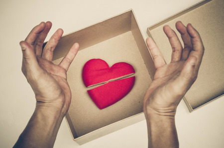 sulk: Broken red heart in a paper box  difficult love and obstacle