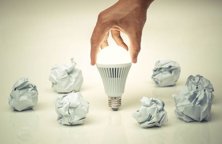business innovation: Hand holding a turned on LED light bulb surrounded by crumpled paper ball  Business with new bright ideas and innovation concept