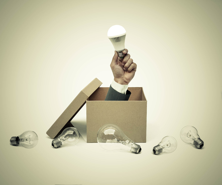 Hand of a businessman holding a turned on light bulb coming out from a brown paper box surrounded by old incandescent light bulbs  Business with new idea and innovation concept
