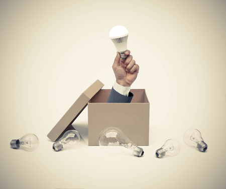new idea: Hand of a businessman holding a turned on LED light bulb coming out from a brown paper box surrounded by old incandescent light bulbs  Business with new idea and innovation concept