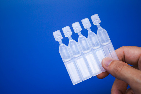lubricant: Lubricant eye drops vials on blue background