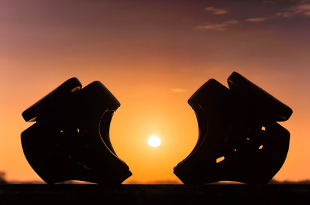 risky love: Red and blue Taekwondo head guards with on sunset silhouette background