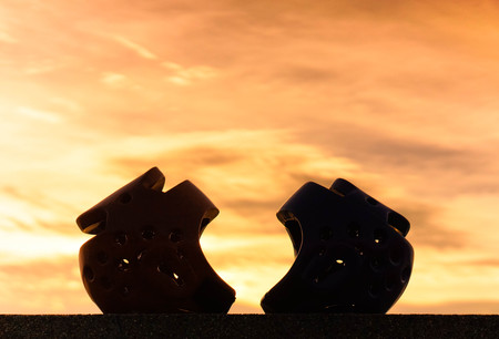 Red and blue Taekwondo head guards with on sunset silhouette background